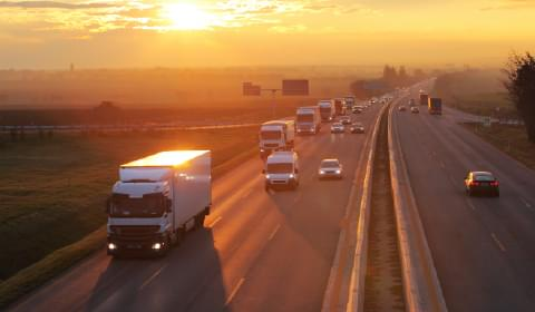 Image of vehicles on a highway at sunset to portray the transportation industry