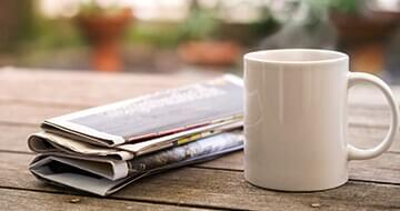 Image displaying folded newspaper and a cup of coffee to represent the company The New York Times