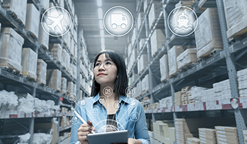 Image of a lady in a warehouse aisle with a tablet computer to portray the Inventory Management case study