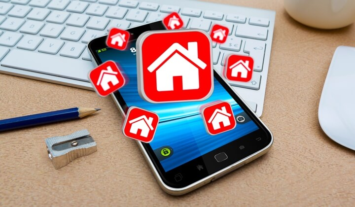 An image of a keyboard, mouse, pencil, sharpener in the background and a mobile phone in the focus with multiple home icons representing the Airbnb network