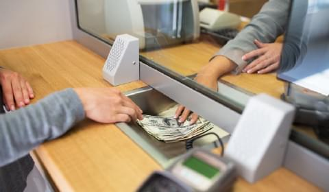 Image of a cashier passing money to a customer in a bank to portray the banking industry