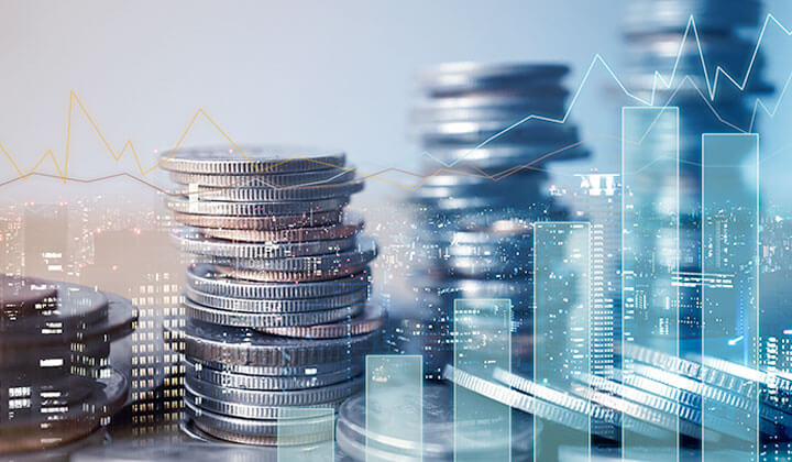 A double exposure image with coins, graphs and charts, to depict the concept of finance