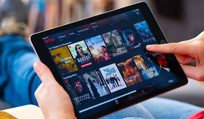 Image of a person looking a tablet with Netflix app on screen