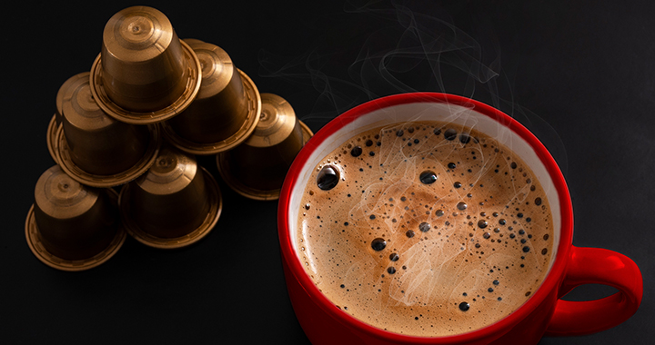Image of coffee capsules and a red cup of hot coffee to portray the case study of Nespresso
