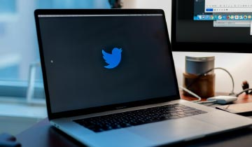 Image of a laptop on a table displaying Twitter logo to portray the case study example.