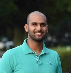 Sovdeep Das smiling wearing a green t-shirt